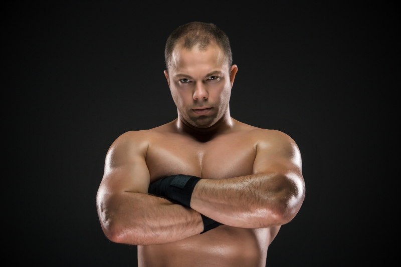 11822099-studio-portrait-of-young-caucasian-boxer-with-folded-hands-posing-ark-background
